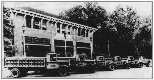 In 1931, Coke was delivered throughout Greenville County by these trucks. They are parked in front of the still heavily treed property just beyond the Greenville Women's College. It served as a community center until  late in the decade, but even after the first extensions, the huge windows allowed passersby a view of the making of the bottled soda.