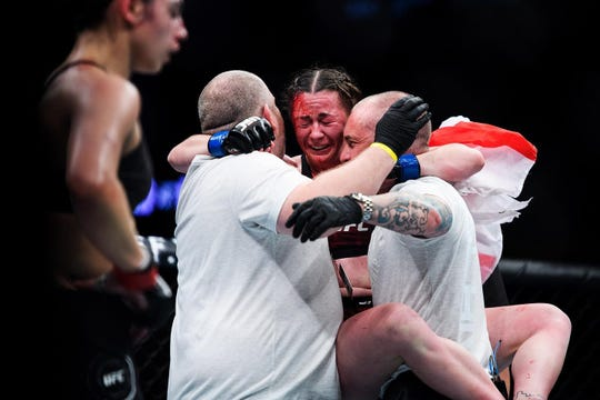 """Meatball"" Molly McCann of Liverpool, England, celebrates her victory at UFC Fight Night 154 in Greenville with her trainers, Paul Rimmer and Simon Audley, Saturday night at Bon Secours Wellness Arena."