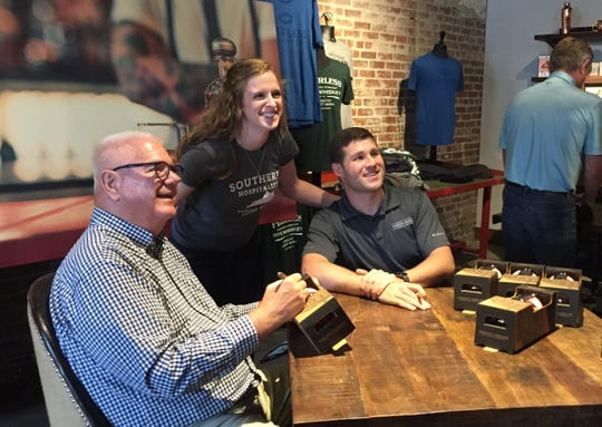 Hendersonian Meredith Stone poses for a photo with Kentucky Peerless CEO Corky Taylor, left, and his master distiller, Caleb Kilburn, while they signed bottles for customers excited to buy the distillery's first new bourbon in more than a century. (Photo by Donna B. Stinnett)