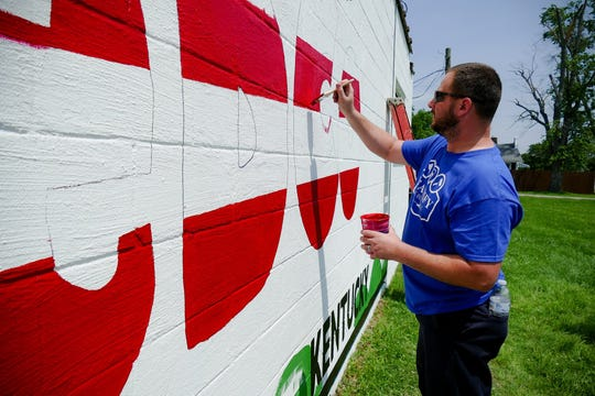 A Big Rivers volunteer paints inside of stenciled letters on the new mural in Sebree, Ky.