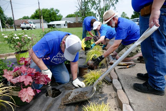 Big Rivers volunteers put in landscaping in the empty lot next to the new mural in downtown Sebree, Ky.