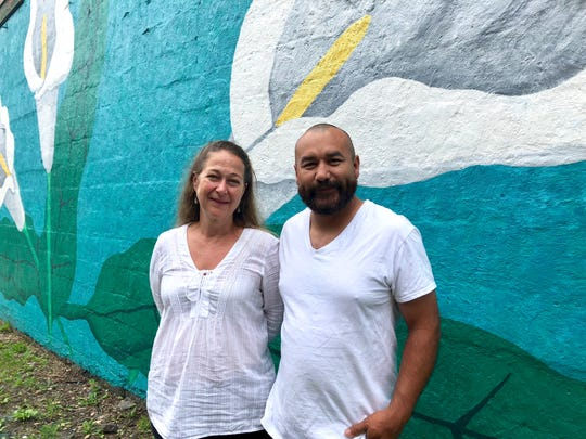 Carranza stands in front of the mural with her husband, Alejandro. Carranza says Alejandro was out with her almost every day, helping to scrape the walls and applying the concrete primer.