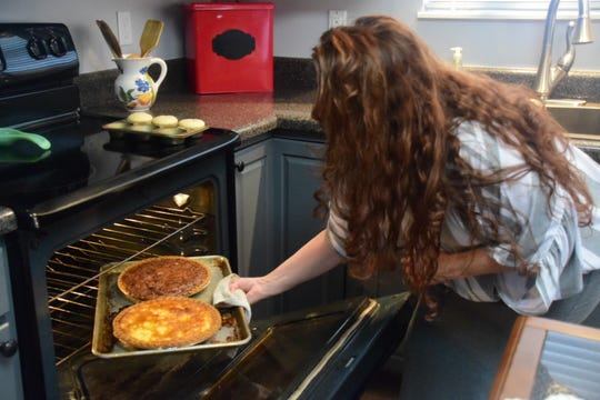 Cindy Ellender removes a freshly baked buttermilk pie and a pecan pie from the oven in Karns on Friday, June 14.