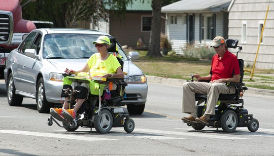 In this 2012 photo, Jan Myers leads West Lafayette Mayor John Dennis on a tour of the city in motorized wheelchairs Thursday.