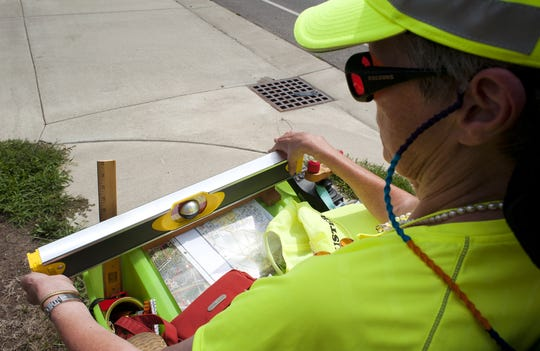 Jan Myers checks to see how level a sidewalk actually is during a 2012 tour of West Lafayette in her power chair.