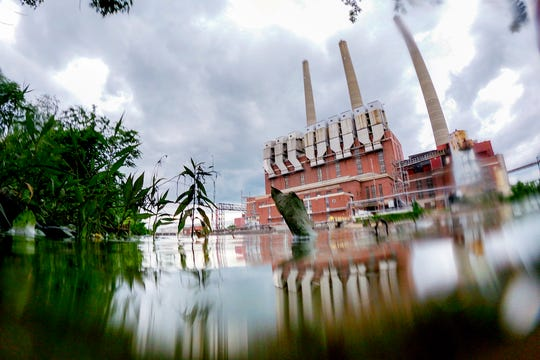 The Grand River flowed Monday by the Eckert Power Plant at Moores Park in Lansing
