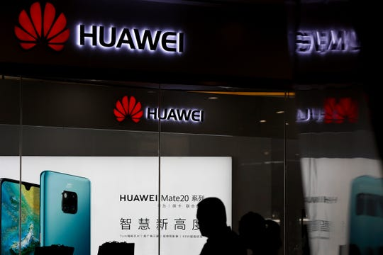 "In this May 29, 2019 file photo, a man walks past a Huawei retail store in Beijing. The Chinese telecom giant is the Commerce Department's  ""Entity List,"" which effectively bars American companies from selling components to Huawei without government approval."