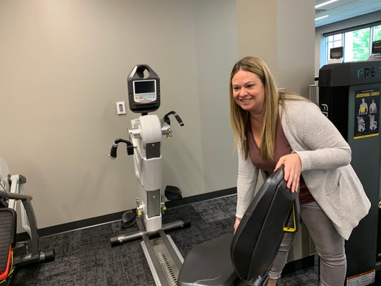 Katie Rehm, vice president of operations for the YMCA of Greater Waukesha County, demonstrates the easy access seat on one of the cardio machines at the New Berlin Wellness Center. The design is important to those members who have mobility limitations, she said.