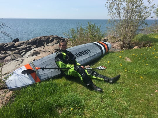 Jared Munch rests during his journey on a stand-up paddleboard across Lake Superior on his way to James Bay in the Arctic Ocean. He expects the trip to take 40 days.