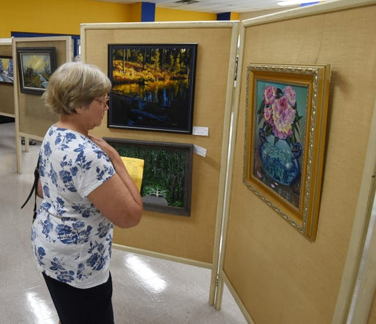 Susan Gamble looks at one of the pieces of artwork on display Friday night at the Area Art Club's 50th annual Art Show.