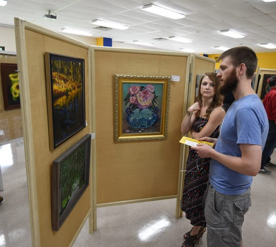 Ben and Alexandra Carlson discuss one of the paintings on display Friday evening at the Area Art Club's 50th annual Art Show.
