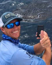 Robert Holzinger, a local fishing charter captain, takes a photo with the whale shark that he encountered Saturday.