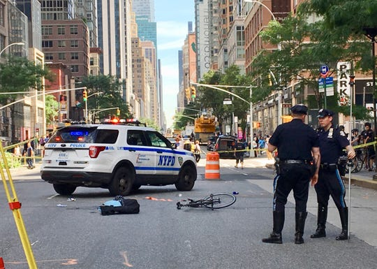 In this photo provided by Meg Maruyama, police stand near the scene of a bicyclist fatality, Monday, June 24, 2019, in the Chelsea neighborhood of New York. The woman was riding on Sixth Avenue when she was struck by a truck. The driver left the scene, according to police.