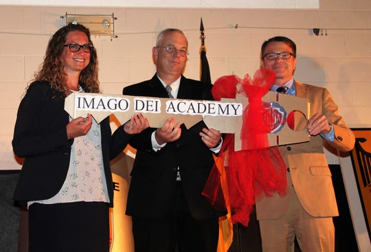 Director of German Military Administration USA/CA Oliver Patrick Weiler presents the key to the German School building in Alamogordo to Imago Dei Academy Headmaster Laura King, left, and Imago Dei Academy Board Chairman Alex Burks at the German School Closing Ceremony Friday, June 21.