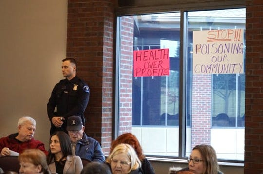 Residents of neighborhoods bordering Arbor Hills Landfill posted signs on the windows of the Northville Township headquarters during a recent meeting.