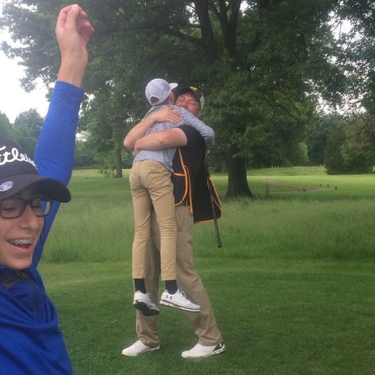 Braylon Park of Howell gets a hug from dad Matt after scoring a hole-in-one in his first tournament.