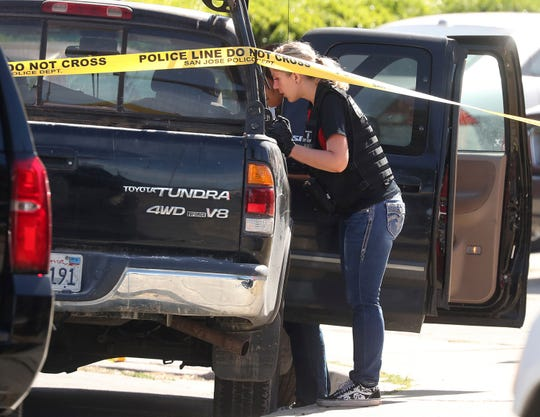 A forensic analyst with the San Jose Police Department searches a truck near scene where five people were killed Monday, June 24, 2019, in San Jose, Calif. A gunman shot and killed four people then turned the gun on himself after an hours-long standoff with police in California, authorities said Monday. San Jose police saw several family members fleeing a home when police responded to multiple calls of shots fired Sunday night.