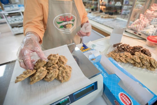 Mary Keller packages pralines Monday at J.W. Renfroe Pecan Co. on Fairfield Drive in Pensacola.