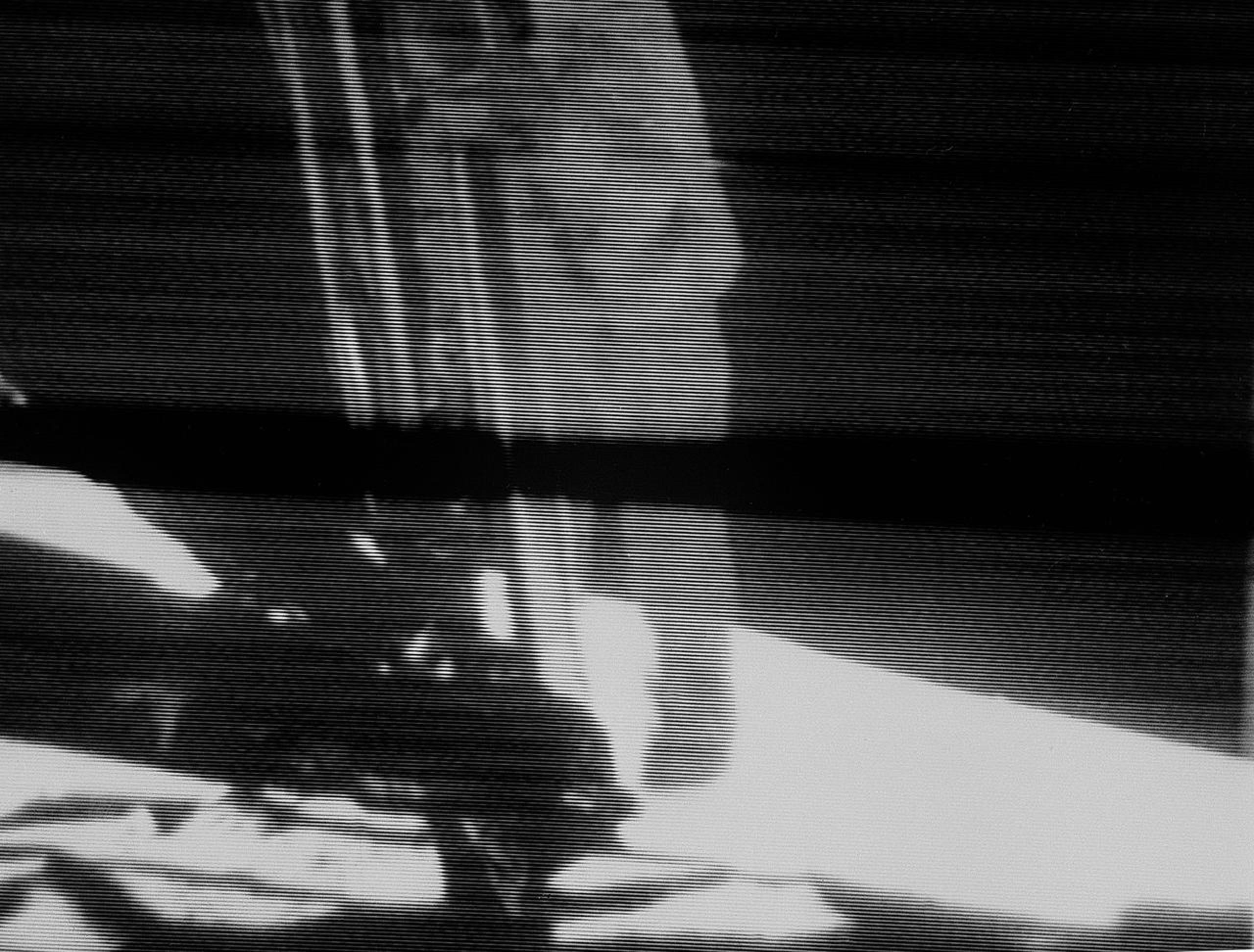 Neil Armstrong, Apollo 11 commander, descends the ladder of the Apollo 11 Lunar Module on July 20, 1969 before making the first step by a human on another celestial body. This view is a black and white reproduction taken from a telecast by the Apollo 11 lunar surface camera. The black bar running through the center of the picture is an anomaly in the television ground data system.