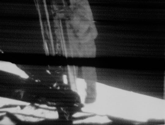 Neil Armstrong, Apollo 11 commander, descends the ladder of the Apollo 11 lunar module on July 20, 1969 before making the first step by a human on the moon. This view is a black-and-white reproduction taken from a telecast by the Apollo 11 lunar surface camera. The black bar running through the center of the photograph is an anomaly in the television data system.