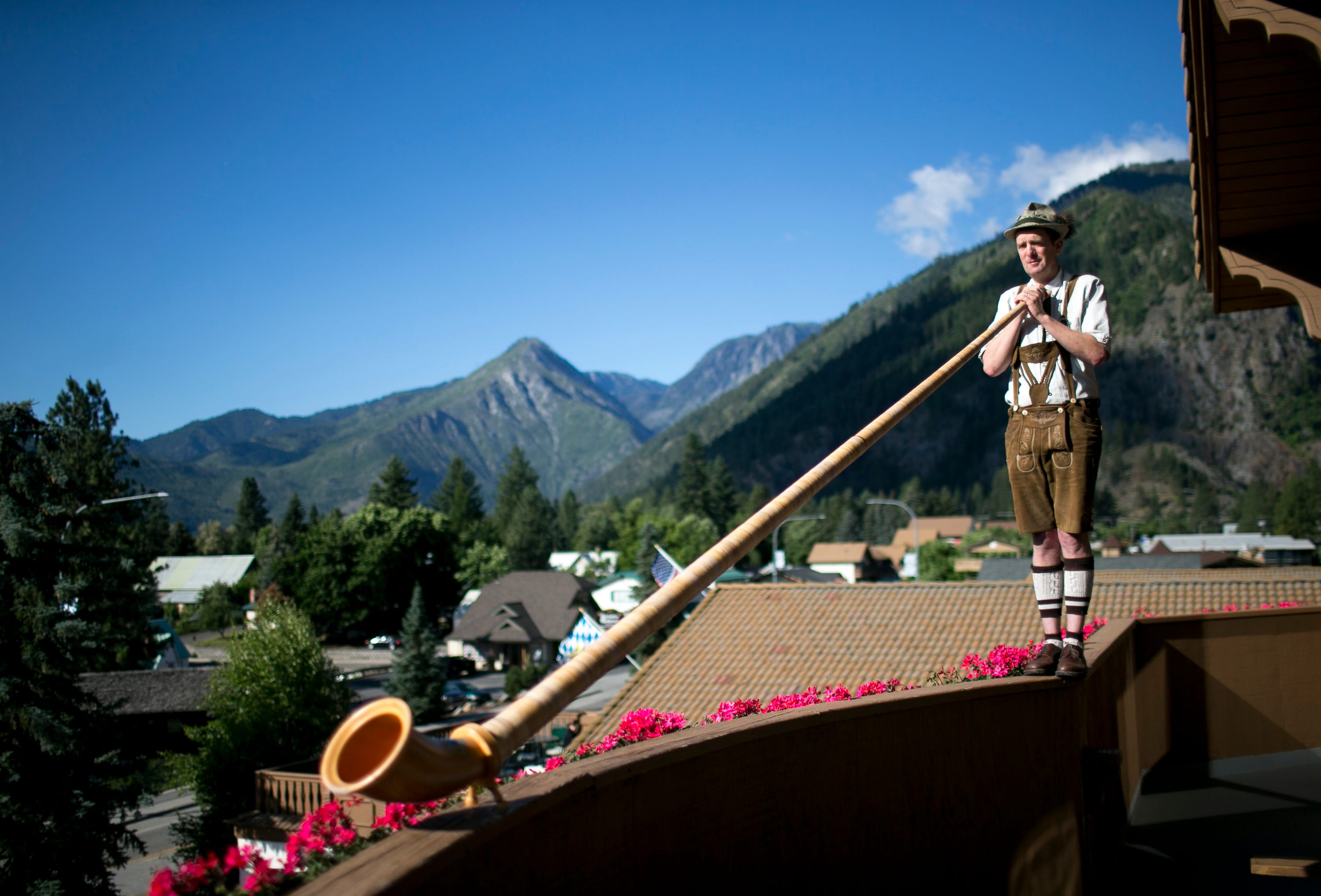 Jordan Brown, general manager at the Enzian Inn, plays an alphorn from the Inn's balcony in Leavenworth, Washington, on June 19, 2019. Leavenworth was stylized into a Bavarian town to promote tourism in the 80s and someone has played the alphorn from hits balcony every morning for nearly 30 years.