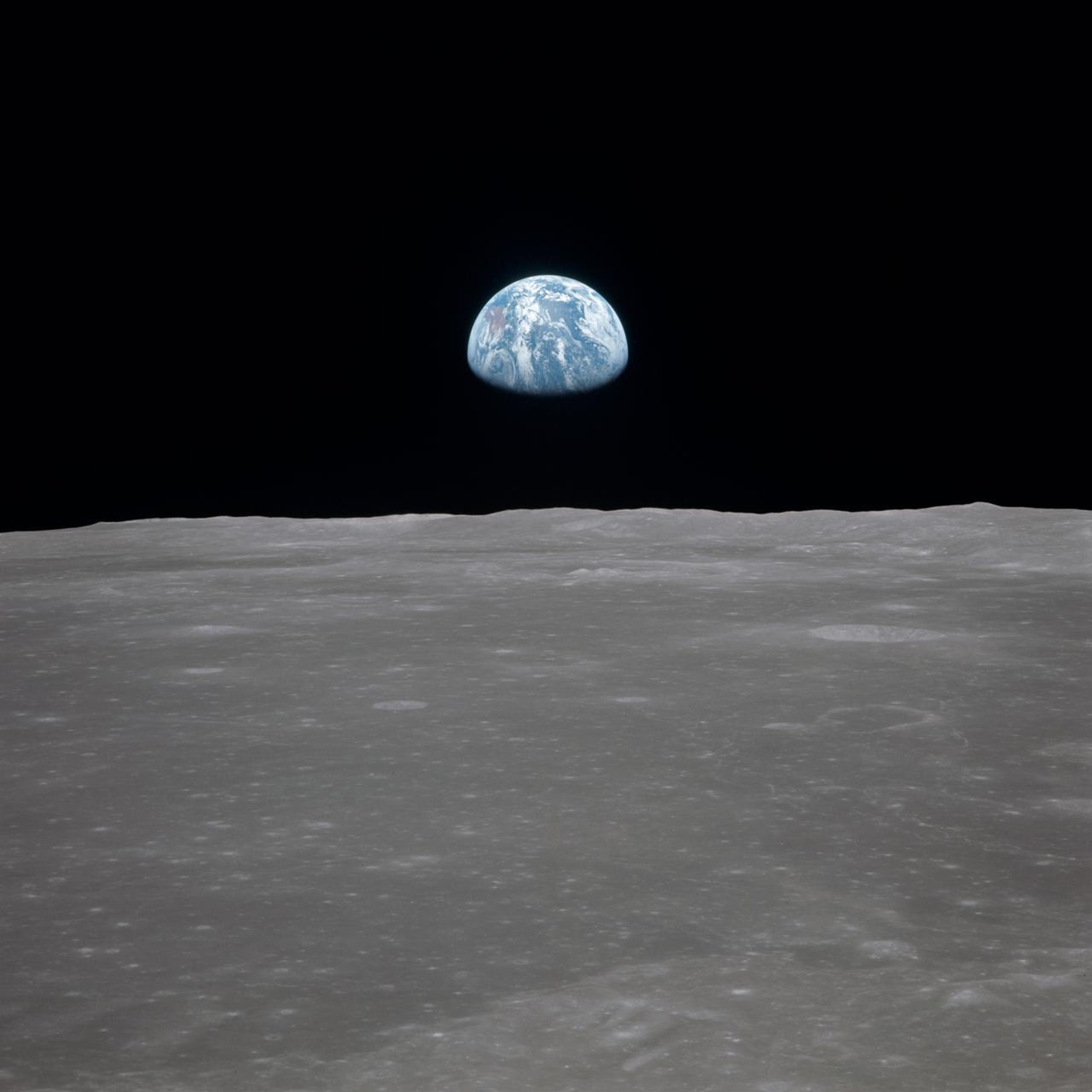 View of the moon with Earth on the horizon, known as the famous Earthrise photo. This image was taken before separation of the lunar module and the command module during Apollo 11 Mission in July 1969.