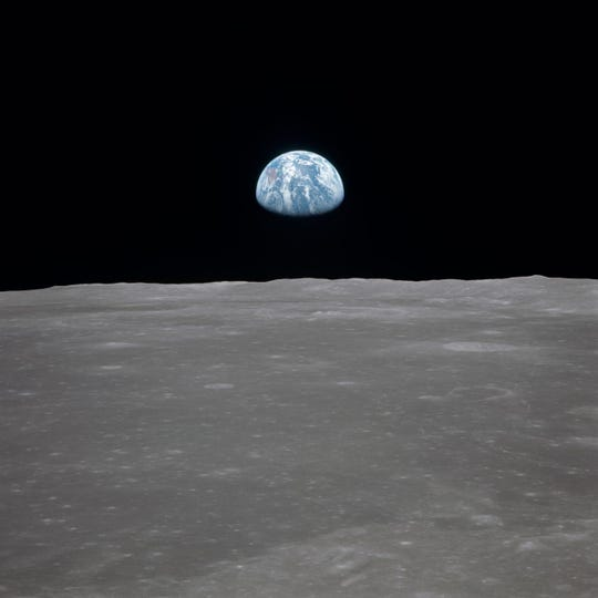 """The famous """"Earthrise"""" photo shows the moon with Earth on the horizon. This photo was taken before separation of the lunar module and the command module during Apollo 11 Mission in July 1969."""