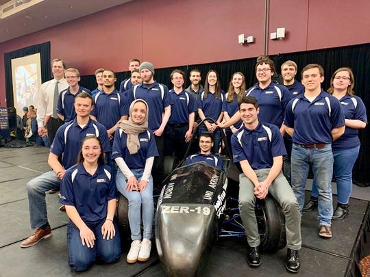 Poughkeepsie's Sean Sheridan sits in the driver's seat as members of the University of Akron electric racing team surround him during an April unveiling of the vehicle they built.