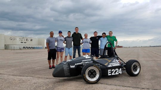 Members of the University of Akron electric racing team pose behind their car. From left: Marcus Caddiell, Natalie Allen, Sean Sheridan, Andrew Penlington, Elena Falcione, Zach Demetriades, Adam Kuhar and Adam Long.