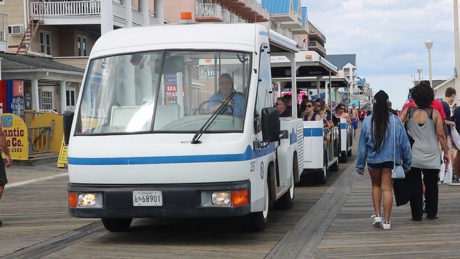 An Ocean City Boardwalk tram passes may visitors on the Ocean City Boardwalk on June 21, 2019.