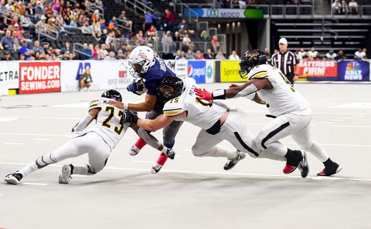 Sioux Falls Storm quarterback Lorenzo Brown jumps through a line of Tucson Sugar Skulls defense in the playoffs Sunday, June 23, at the Denny Sanford Premier Center in Sioux Falls.