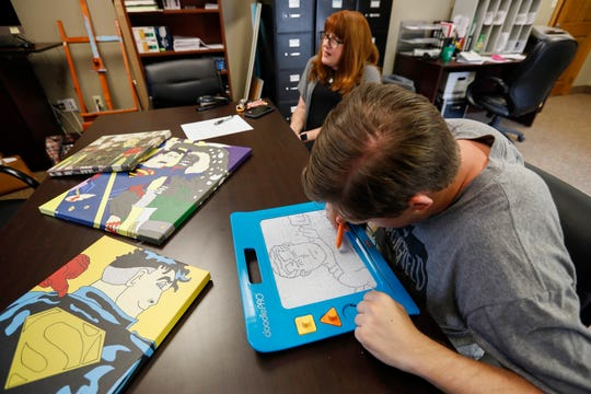 Connor McGranahan draws a picture of Superman on his magnetic drawing board at the Abilities First office on June 21.