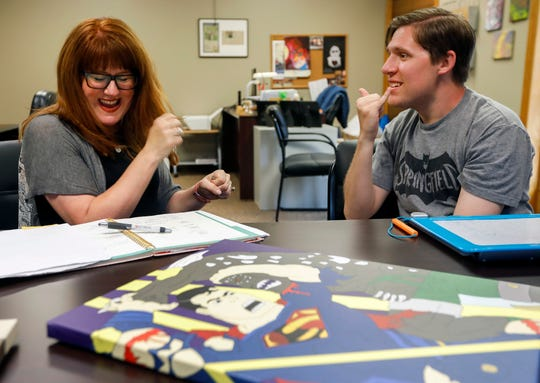Connor McGranahan, right, signs with his mom Jamie McGranahan at the Abilities First office on  June 21.