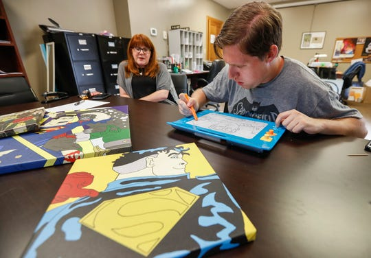 Connor McGranahan draws a picture of Superman on his magnetic drawing board at the Abilities First office in Springfield, Mo., on Friday, June 21, 2019.