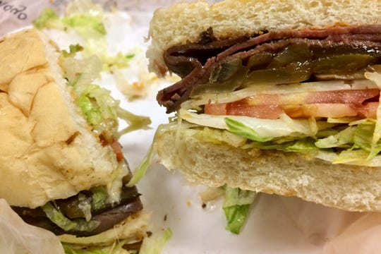 Hopkins' smothered beef sandwich, with layers of sliced roast beef topped with sautéed green peppers, onions, mushrooms and Swiss and Parmesan cheeses plus mayo, lettuce, tomato and a Parmesan dressing.