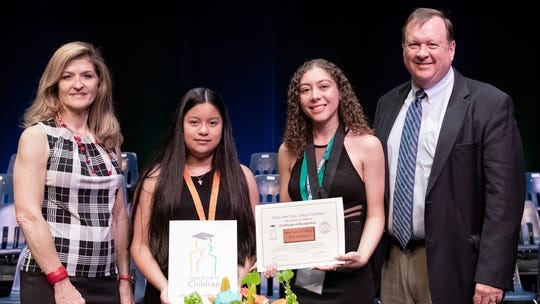 "Susan Klein, left, and Michael Minton, right, stand with the Take Stock in Children Robert ""Bobby"" Klein Memorial Endowment Scholars Karla Castro and Elysa Jenkins."
