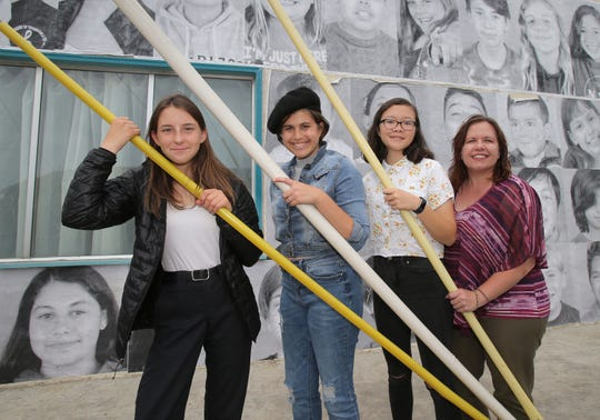Ruby Lacques, from left, Naia Leonetti and Carina Ziesk, students from De Anza Academy of Technology and the Arts, pose with their visual art and yearbook adviser Christa Bandringa in front of the photo mural that they helped put together on the side of the old Avenue Hardware building located on Ventura's Westside. Lacques was the project director and Leonetti and Ziesk, with the help from Cash Merriman and Lukas Pedroza, were the photographers.