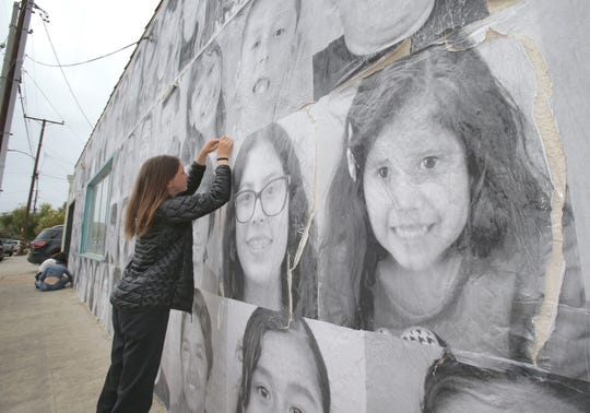 Ruby Lacques, a student a De Anza Academy of Technology and the Arts,  works on repairing the photo mural that she and a few of her fellow classmates had made on the side of the old Avenue Hardware building located on Ventura's Westside. Lacques was the project director that included photos of kids from the neighborhood.