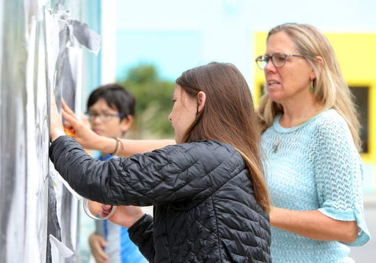 Ruby Lacques, a student a De Anza Academy of Technology and the Arts,  works on repairing the photo mural on the side of the closed Avenue Hardware building located on Ventura's westside. The building's new owner Lorelei Woerner-Eisner looks on.