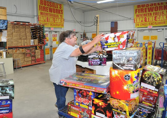 Russell's Fireworks, employee, Kim Goolsby rings up a large cart of fireworks Monday morning after opening their doors for the July 4th holiday.