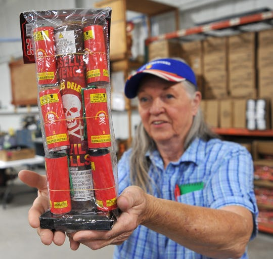 Patsy Hodgkins, owner of Russell's Fireworks shows one of their most popular products called Russell's Revenge. Hodgkins said customers receive a free package of Russell's Revenge with every $50 purchase.