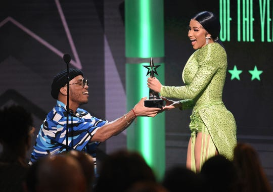 Anderson .Paak presents the album of the year award to Cardi B at the BET Awards.