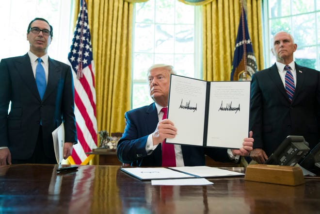President Donald Trump holds up a signed executive order to increase sanctions on Iran on Monday in Washington. Trump is accompanied by Treasury Secretary Steve Mnuchin, left, and Vice President Mike Pence.