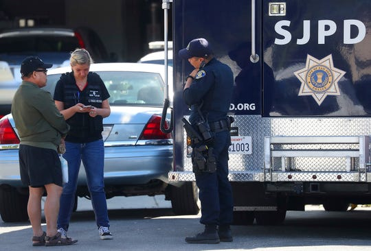Members of the San Jose Police Department talk with an unidentified man, left, near the scene where five people were killed Monday, June 24, 2019, in San Jose, Calif. A gunman shot and killed four people then turned the gun on himself after an hours-long standoff with police in California, authorities said Monday.