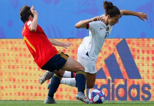 June 24: U.S. forward Carli Lloyd (10) battles for the ball with Spain midfielder Marta Corredera.