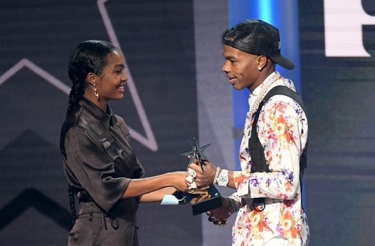 """""""Grown-ish"""" star Yara Shahidi, left, hands the Best New Artist award to Lil Baby at the BET Awards on Sunday."""