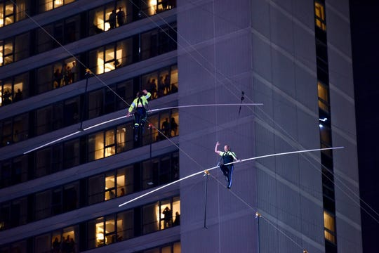 Lijana Wallenda and Nik Wallenda walk a high wire over Times Square on Sunday night.