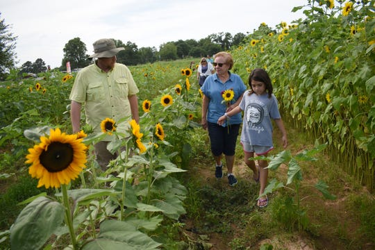 Cliff Dailey (left) and daughter Julia Dailey (right) show Frances Boudreaux and her family around Aunt Julia's Garden. The garden is located on the corner of Messina Road and Highway 28 West.