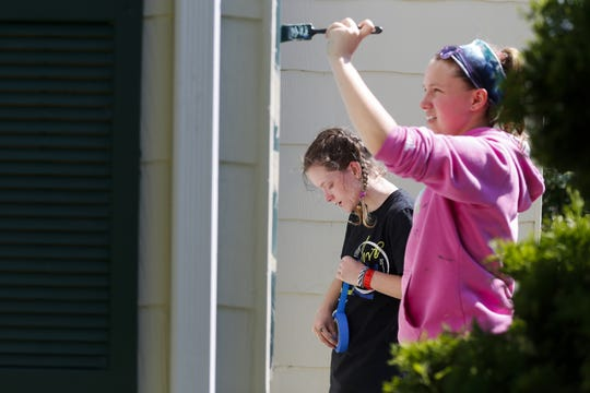 Jillian King (middle) and Jordan Tousignant paint a home in Freedom as part of a week long mission trip with TeenServe youth group.