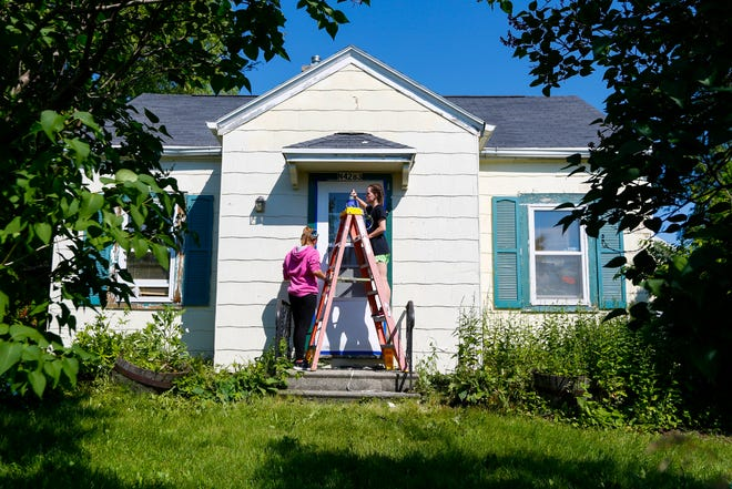 Jillian King (right) and Jordan Tousignant paint a home in Freedom as part of a week long mission trip with TeenServe youth group.